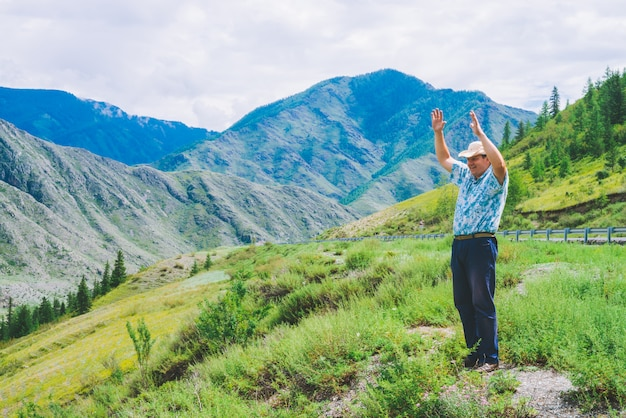Joyous man near highway among giant mountains. cheerful traveler on hill among rich vegetation. mountain tourism. journey in highland.