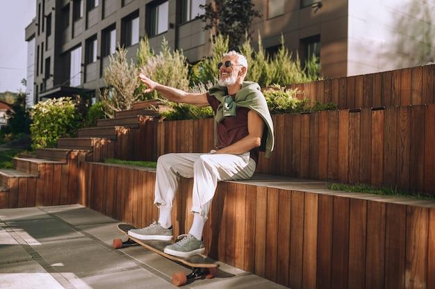 屋外で楽しんでいる楽しい成熟した男性のスケートボーダー