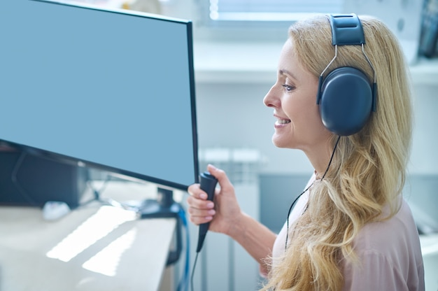 Joyous middleaged blonde lady undergoing a hearing screening procedure