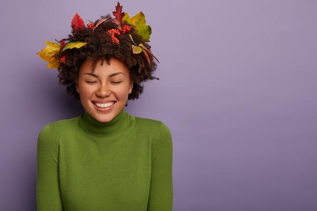 うれしそうな大喜びのアフリカ系アメリカ人女性は、特定の外観を持ち、優しく微笑んで、新しい服を着て、巻き毛の葉、紫色の背景に対してスタジオでポーズをとり、彼女の体に沿って手を保ちます