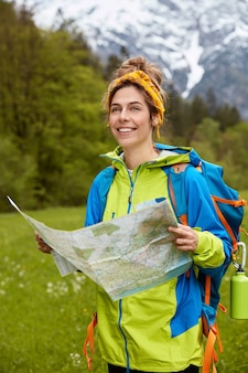 Joyous pleased young woman dressed casully, reads map, finds necessary location, considers route
