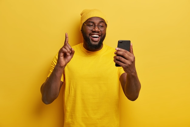 즐거운 통통한 남자가 검지 손가락을 들고 휴대 전화를 들고 인터넷 서핑을위한 여가 시간을 즐기고 노란색 모자와 캐주얼 티셔츠를 입습니다.