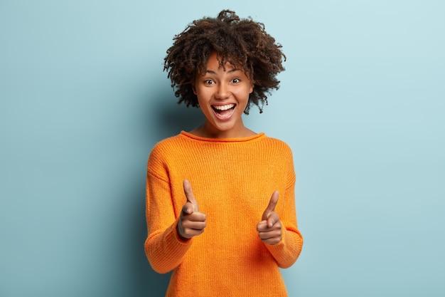 Радостная симпатичная афроамериканка показывает пальцем пистолет на камеру, выражает выбор, широко улыбается, одетая в оранжевый джемпер