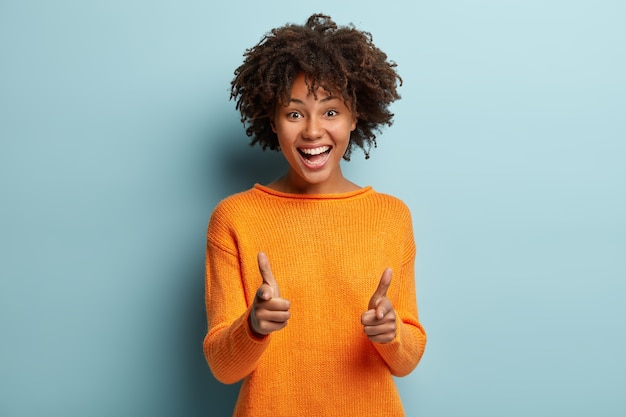 Joyous pretty african american lady makes finger gun gesture at camera, expresses choice, smiles broadly, dressed in orange jumper