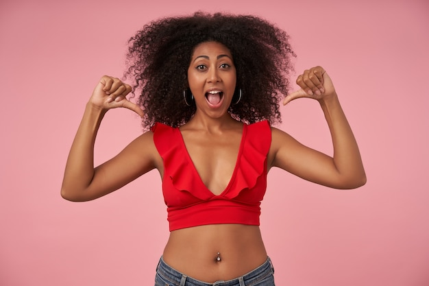 Joyous pretty curly lady with dark skin having belly button piercing pointing on herself with raised thumbs, joyfully with wide mouth opened, posing on pink
