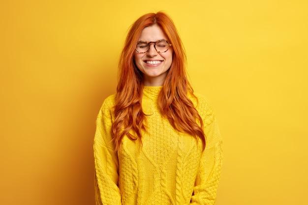 Радостная симпатичная женщина с рыжими волосами закрывает глаза, довольная стоит, одетая в повседневный джемпер, носит оптические очки, напоминает что-то очень приятное.