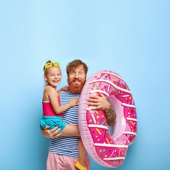 Joyous red haired family have fun at coastline. pleased cheerful bearded dad holds little girl and inflated swim ring