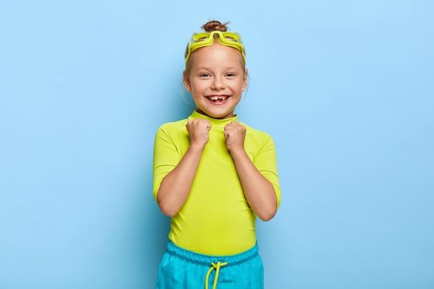 Gioiosa piccola femmina alza i pugni chiusi, si rallegra del nuoto di successo, indossa occhiali protettivi, vestiti luminosi, ha un sorriso a trentadue denti, gode del suo hobby preferito durante le vacanze estive. infanzia felice