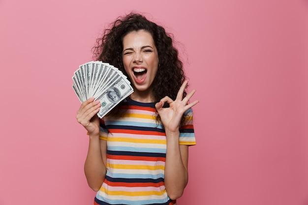ピンクで隔離されたドルのお金のファンを保持している巻き毛の楽しい女性20代