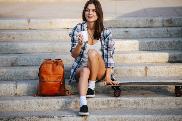 Joyous woman sitting on the stairs next to her skateboard having a rest