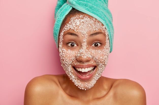 La donna gioiosa sorride positivamente ha gli occhi delle sopracciglia, si prende cura della pelle del corpo, indossa uno scrub al sale marino per pulire la carnagione