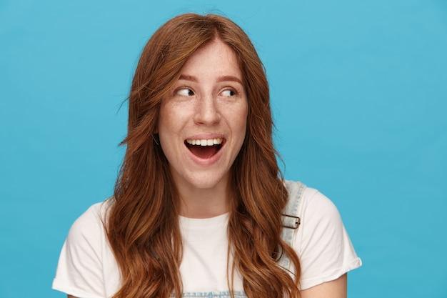 파란색 배경 위에 서있는 동안 기본 흰색 티셔츠를 입고 넓은 미소로 유쾌하게 옆으로 보이는 물결 모양의 헤어 스타일을 가진 즐거운 젊은 아름다운 빨간 머리 여자