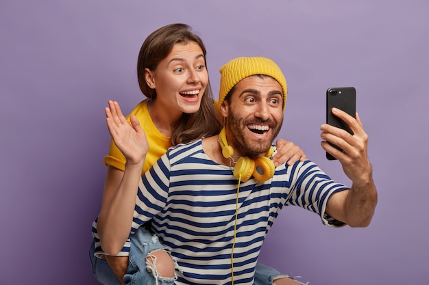 Joyous young couple make video call, hold smartphone in front, guy gives piggyback to girlfriend who waves palm in camera of cellular, pose together against purple background