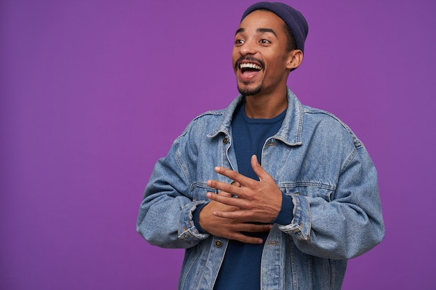 Joyous young handsome dark skinned bearded brunette male smiling joyfully and looking happily aside, dressed in casual clothes while posing over purple wall
