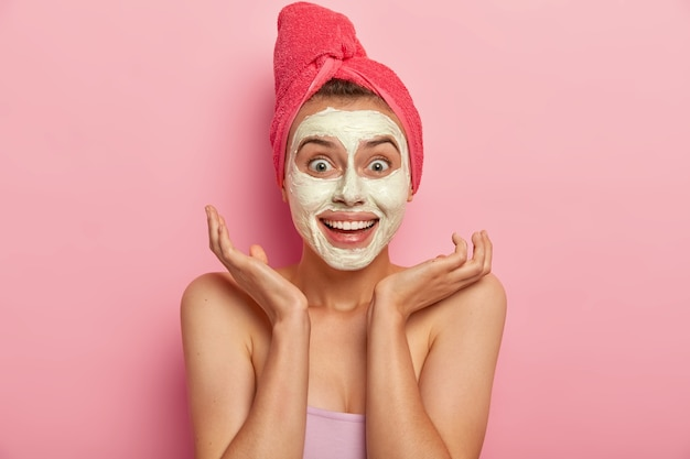 Gioiosa giovane donna con un'espressione allegra, allarga i palmi vicino al viso, applica una maschera all'argilla naturale per sembrare rinfrescata, ha un sorriso affascinante, avvolto in un morbido telo da bagno