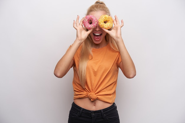 Joyous young long haired blonde slim woman fooling while standing against white background, looking at camera through colored donats and laughing cheerfully with wide mouth opened