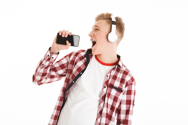 Joyous young man  in casual t-shirt listening to music via wireless earphones and singing using smartphone like microphone, isolated over white wall