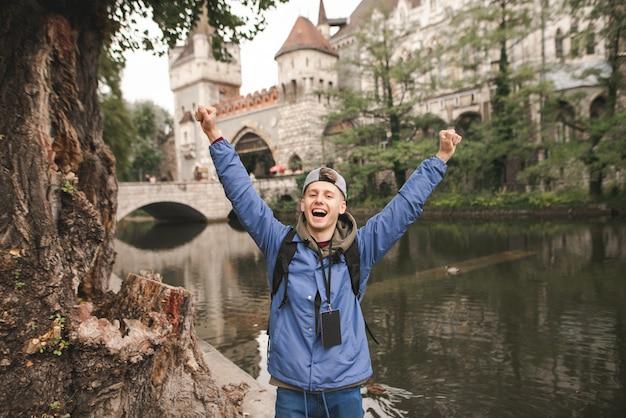 즐거운 젊은 관광객은 vajdahunyad castle에서 자른 그의 손으로 기뻐합니다.