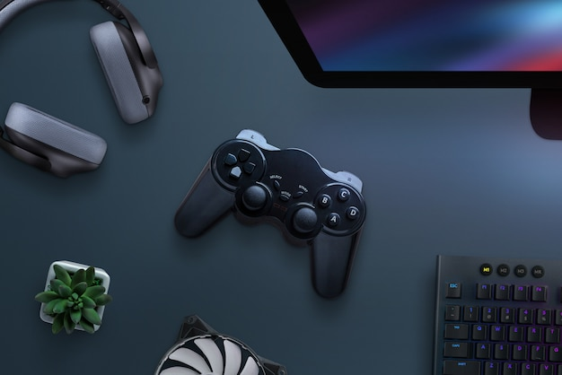 Joypad on desk surrounded with headphones, cooler, keyboard and computer display. pc gaming concept. top view, flat lay.