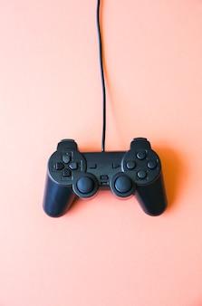 분홍색 배경에 누워 있는 조이스틱. 컴퓨터 게임을 위한 게임패드.