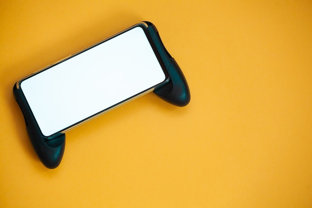 조이스틱 휴대 전화, 노란색 배경 상위 뷰에 격리된 화면 모형