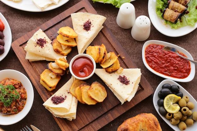 Вид сверху жареная картошка с кетчупом, черными и зелеными оливками, хлеб, баклажаны, рулетка, жареный овощной салат, соль и перец на столеjpg