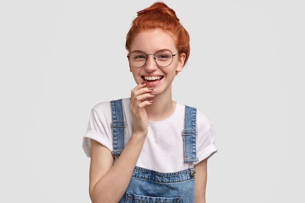 Jubilant beata signora zenzero lentigginosa indossa occhiali rotondi, sorride delicatamente, tiene la mano sul mento, ha la pelle lentigginosa, vestito con abiti casual, isolato su un muro bianco