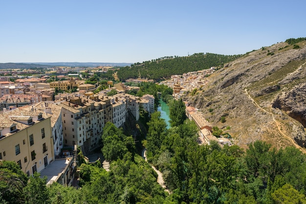 The jucar river surrounds the city of cuenca castilla la mancha forming a gorge full of green trees