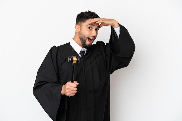 横を見ながら驚きのジェスチャーをしている白い背景で隔離のアラブ人裁判官