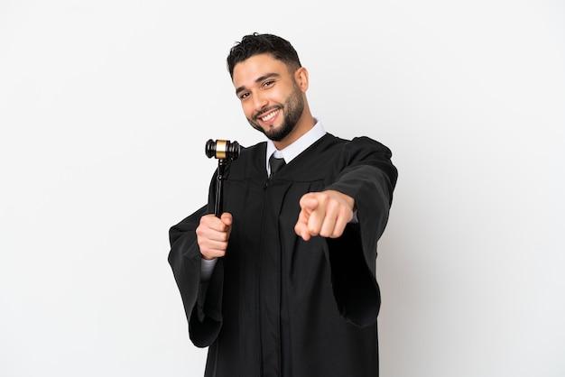 Судья арабский человек изолирован на белом фоне, указывая спереди с счастливым выражением лица