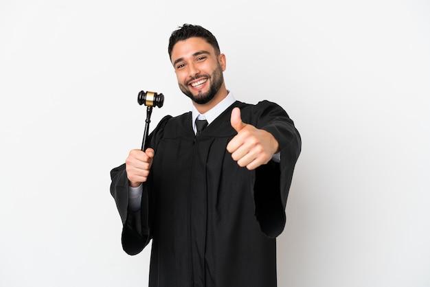 何か良いことが起こったので、親指を立てて白い背景に孤立したアラブ人裁判官