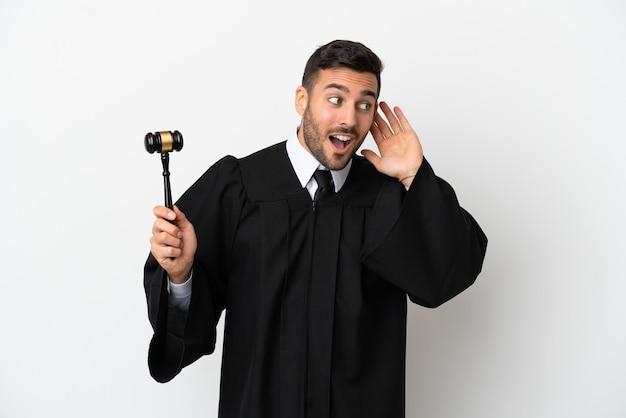 Судья кавказский человек изолирован на белом фоне, слушая что-то, положив руку на ухо