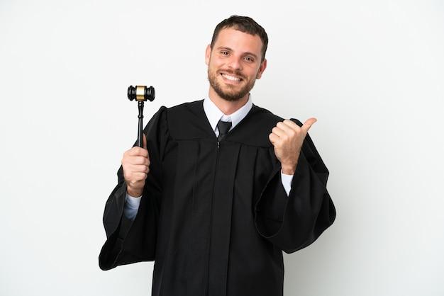 Судья кавказский человек изолирован на белом фоне, указывая в сторону, чтобы представить продукт
