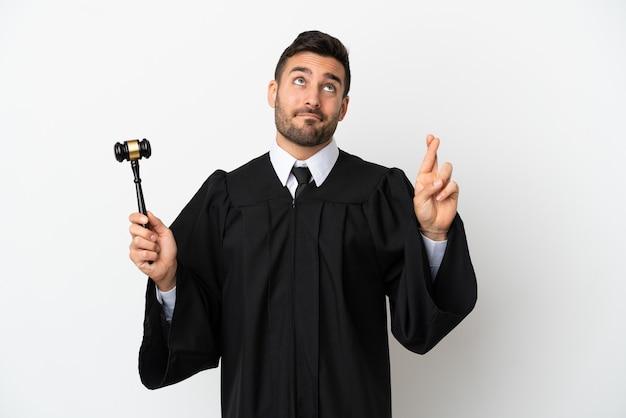 Судья кавказский человек изолирован на белом фоне со скрещенными пальцами и желает лучшего