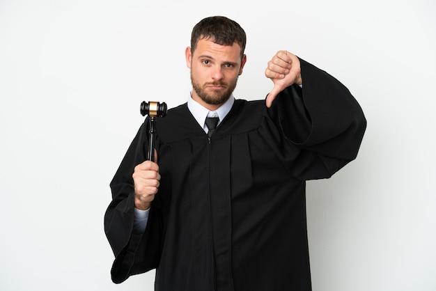 부정적인 표현으로 아래로 엄지 손가락을 보여주는 흰 벽에 고립 된 백인 남자 판사