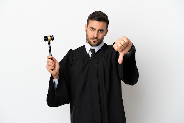Judge caucasian man isolated on white background showing thumb down with negative expression