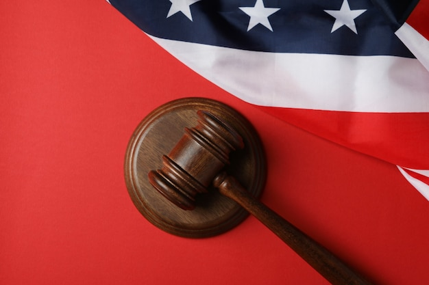 Judge gavel and american flag on red background