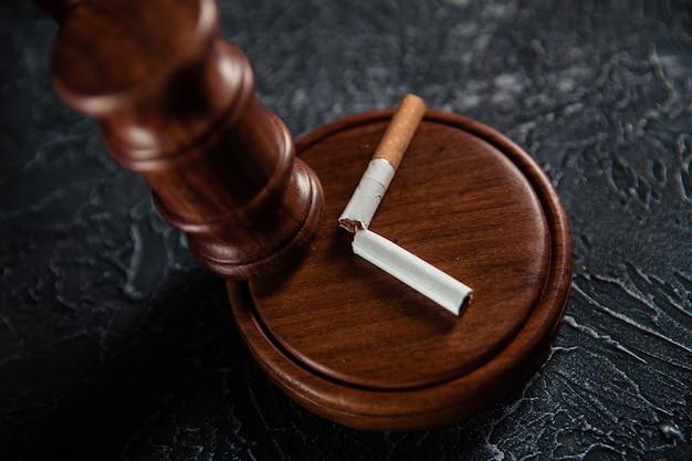 灰色の表面に小槌と壊れたタバコを判断します。たばこ法