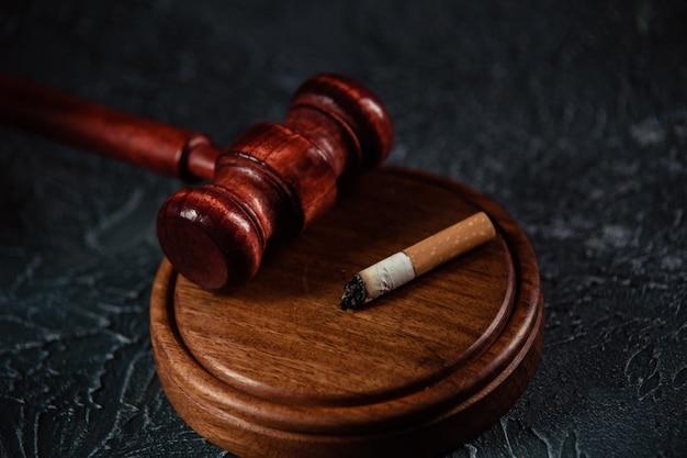 灰色のテーブルで小槌と壊れたタバコを判断します。たばこ法