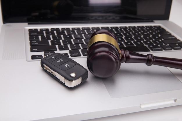 Молоток судьи и ключ от машины на клавиатуре ноутбука. символ закона, справедливости и интернет-аукциона