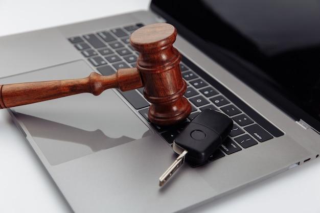 Молоток судьи и ключи от машины на клавиатуре портативного компьютера. символ закона, справедливости и интернет-аукциона автомобилей.