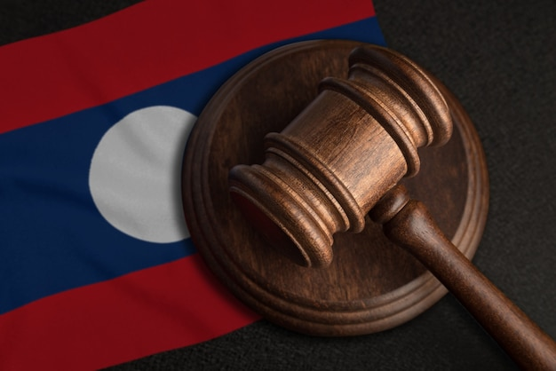 Судейский молоток и флаг лаоса. закон и справедливость в лаосе. нарушение прав и свобод.