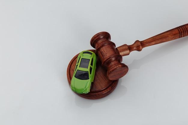 Молоток судьи и зеленый игрушечный автомобиль на белой предпосылке. символ закона, справедливости и автомобильного аукциона.