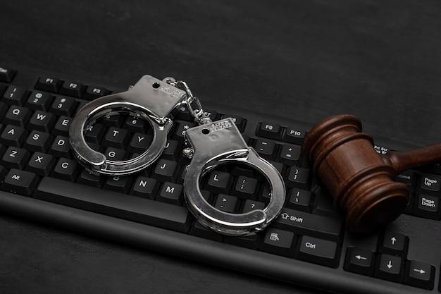 판사 망치와 컴퓨터 키보드에 수갑입니다. 사이버 범죄 . 인터넷상의 법적 책임. 온라인 불법 복제.