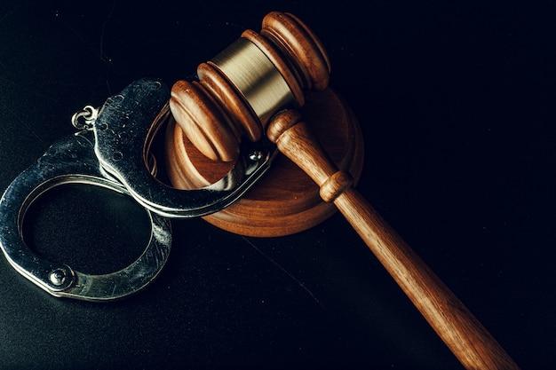 Судья молоток и наручники на темно-черной поверхности