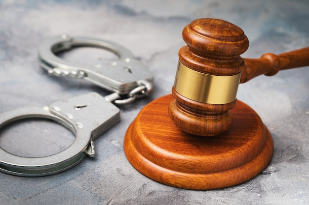 Судья молоток и наручники на концепции правосудия стола