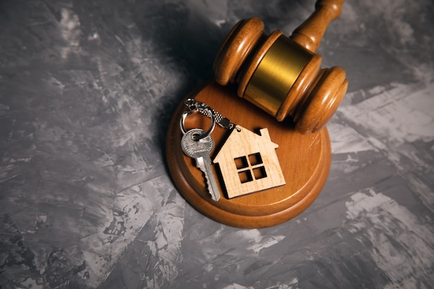 灰色の背景にガベルと家の鍵を判断します。不動産法の概念
