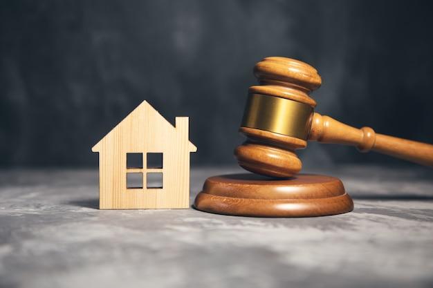 裁判官のガベルと家のモデル。不動産法の概念