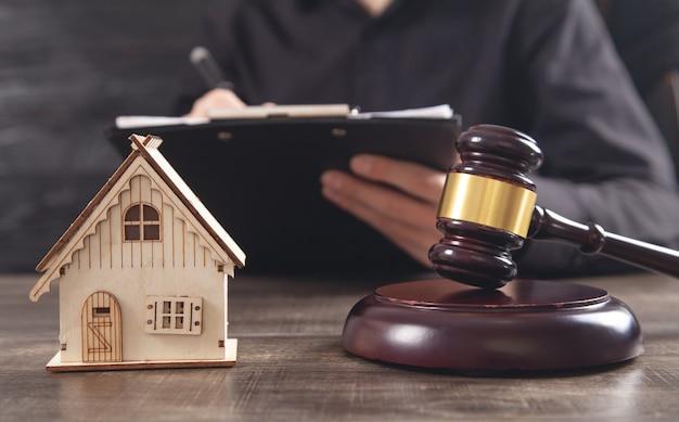 テーブルの上のガベルと家のモデルを判断します。ドキュメントにサインインする男性。不動産弁護士