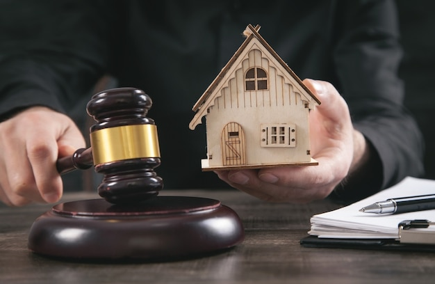 Судейский молоток и модель дома на столе. юрист по недвижимости